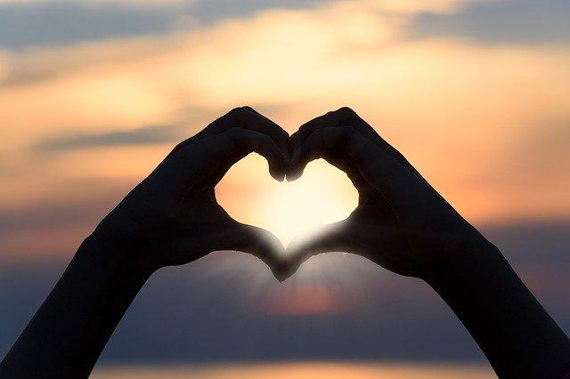 Twee handen die samen een hartje vormen met hun vingers